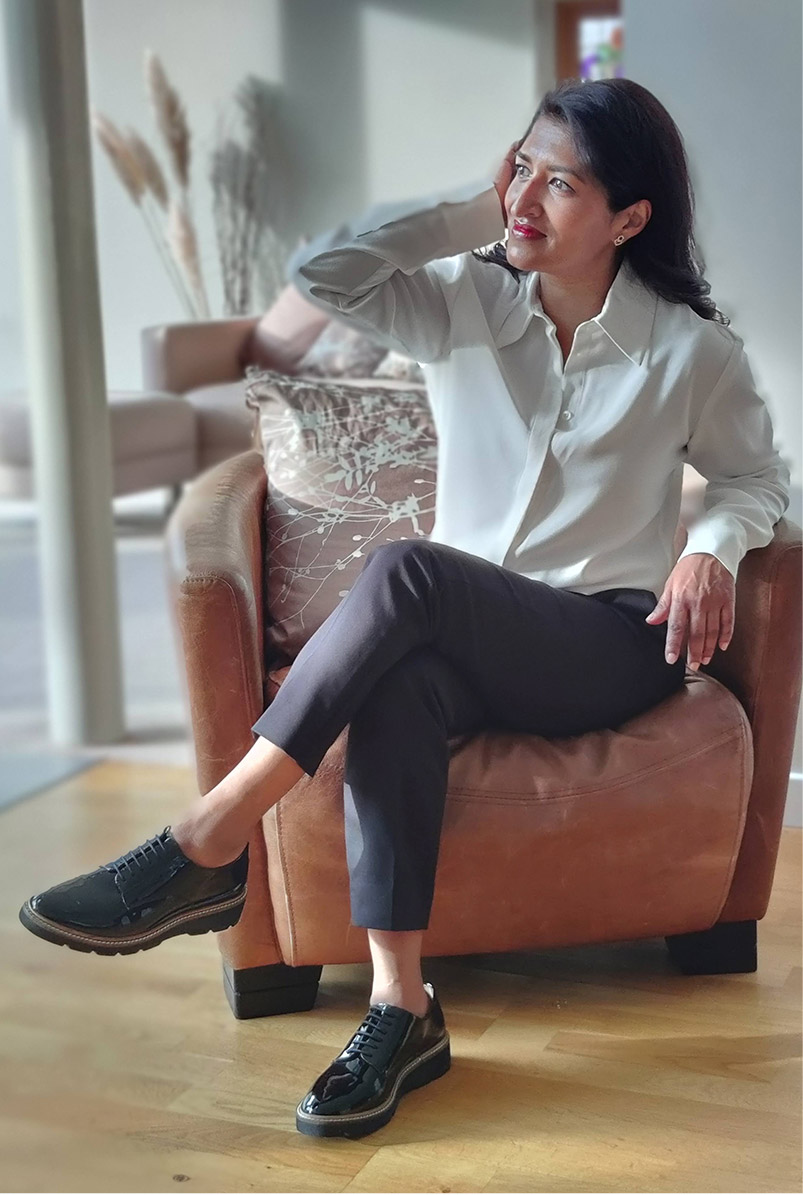Photographed at home, fashion blogger Monika Mandal wears Hobbs Eva silk shirt, petite Quin navy trousers and Bloomsbury black patent lace-up shoes.