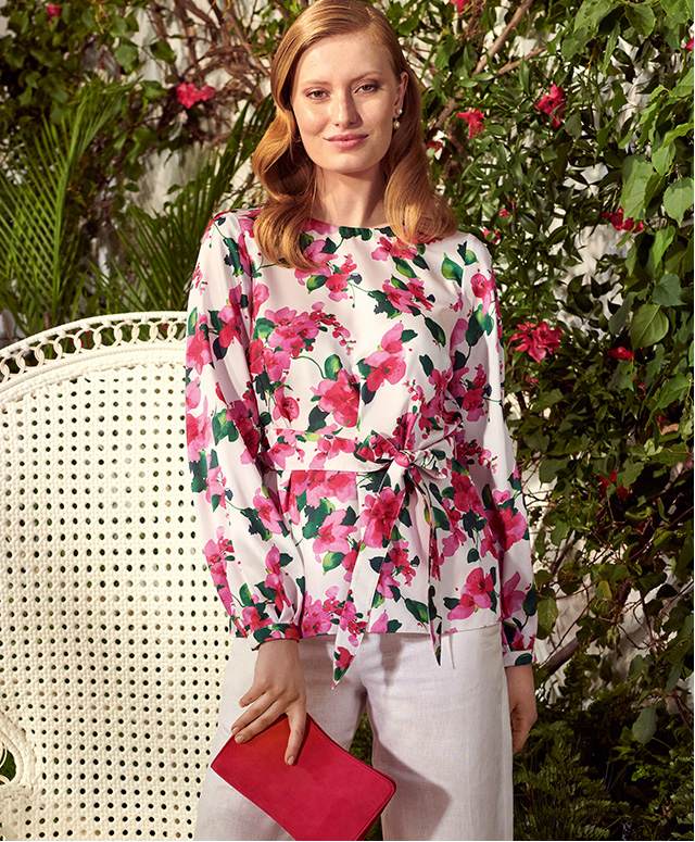 Model photographed wearing Hobbs Rosie bougainvillea floral print top with white linen trousers.