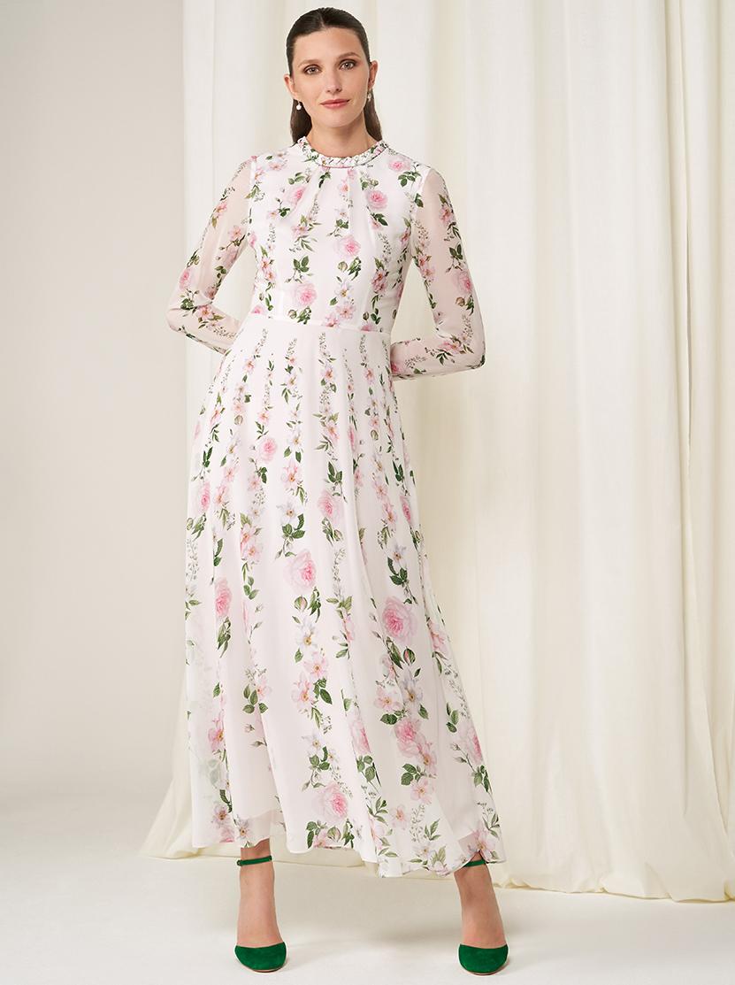Model wears a floral silk midi dress and heels.