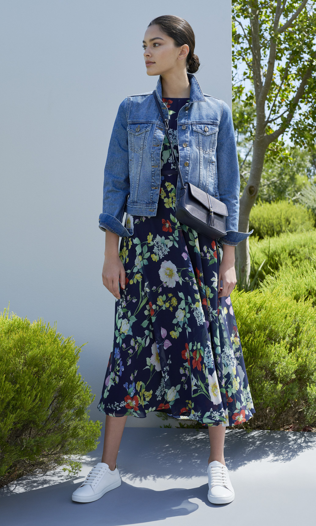 Woman poses in a dark blue floral midi dress styled with a light blue denim jacket, white leather trainers with a navy blue leather cross body bag.