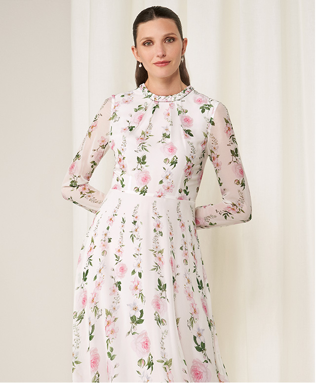 Model photographed wearing Hobbs Rosabelle silk dress with a rose and blossom floral print.