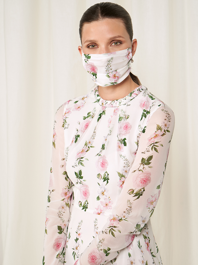 Model wears a floral silk midi dress and a face mask.