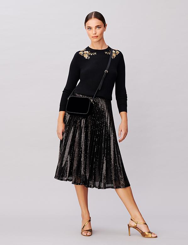 Golden Floarl Embellished Black Jumper on Sparkling Pleated Skirt with Gold Sandals and Small Black Crossbody Bag