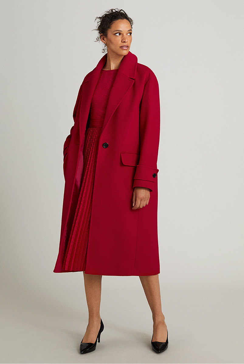 Model wears a red midi dress with a red coat and heels.
