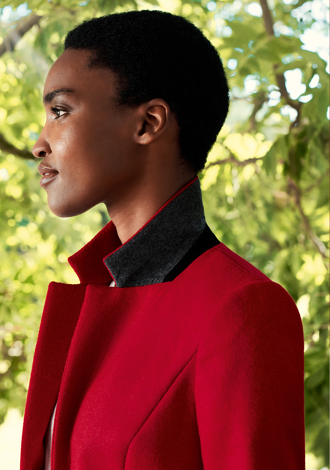 Close-up image of model wearing a Hobbs red jacket with the collar turned up.