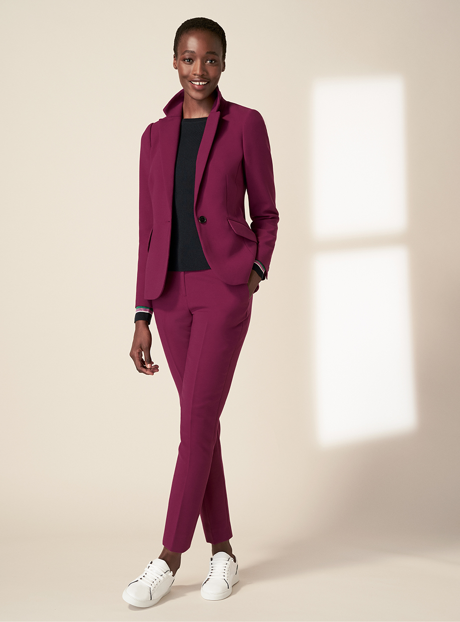 Model wearing Hobbs' Suki magenta pink tailored jacket and matching trousers with trainers.
