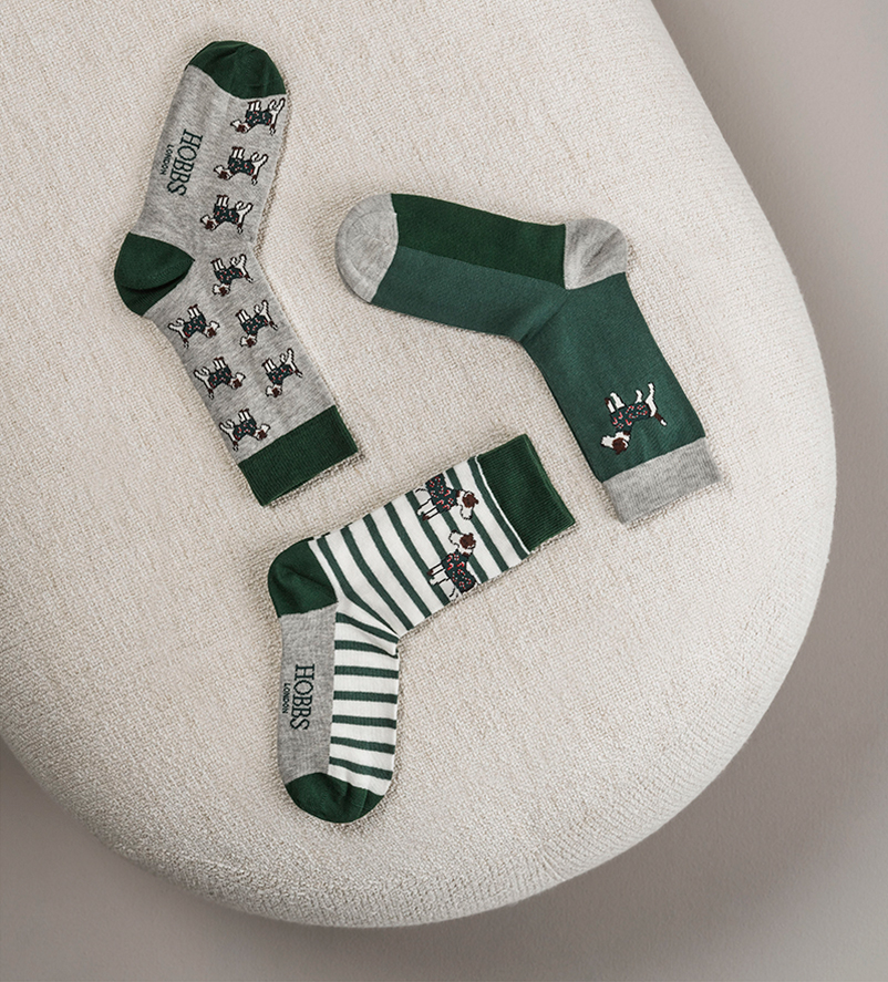 Set of 3 socks with a dog motif displayed on a footstool.