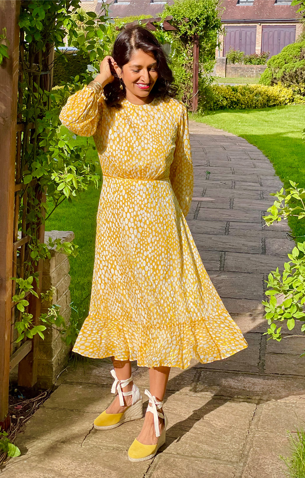 Fashion blogger @monikagoestowork photographed in her garden wearing Hobbs' Lexi yellow jacquard dress.