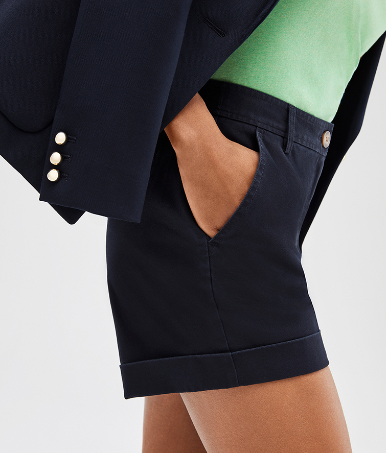 Detail shot of model in navy shorts, green pixi tee and navy blue martina jacket