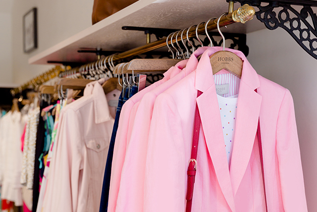 A clothing rail in a Hobbs store, featuring a pink blazer, a white dotted top underneath and the strap of a red leather crossbody bag on a hanger and other garments in the background.