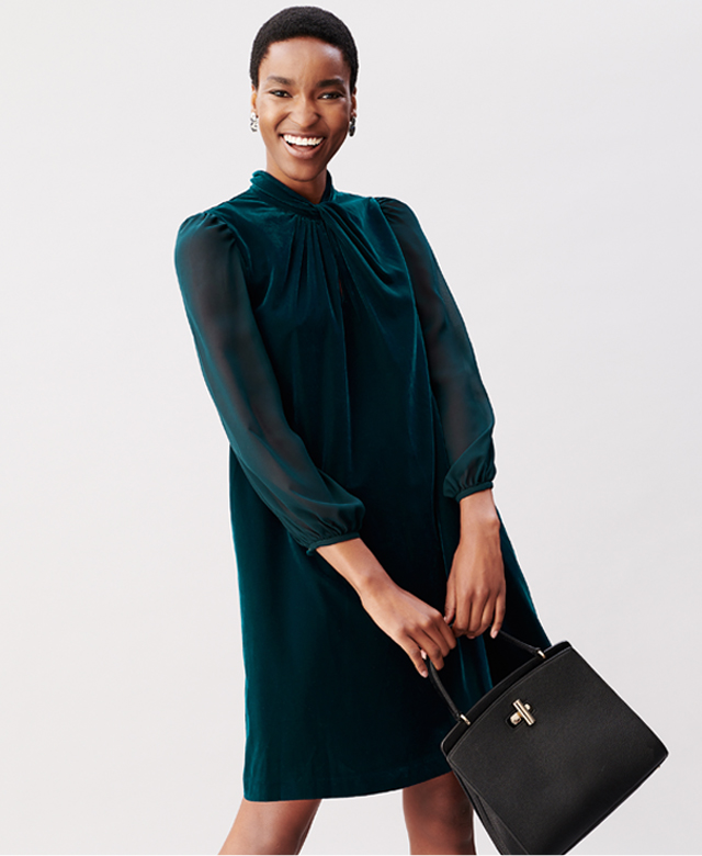 Model photographed wearing a dark green velvet dress holding a black bag.
