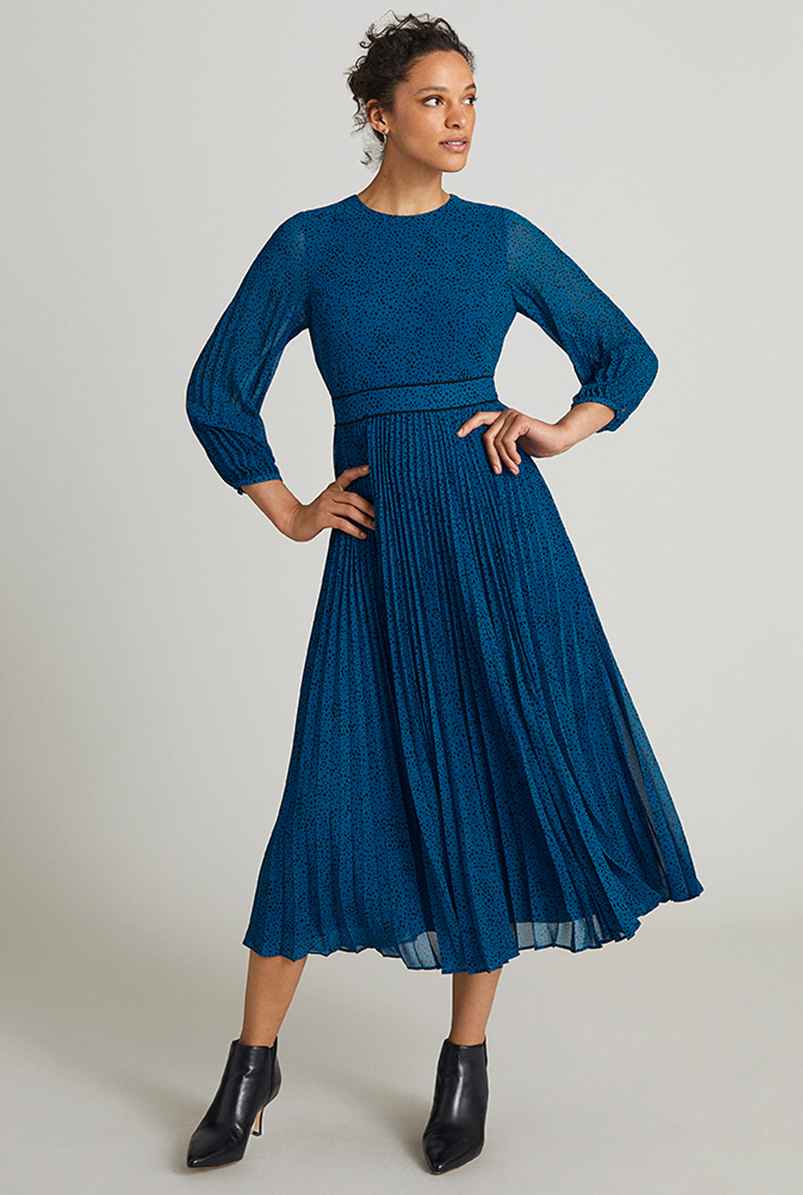 Model wears a blue long-sleeved printed midi dress with ankle boots.