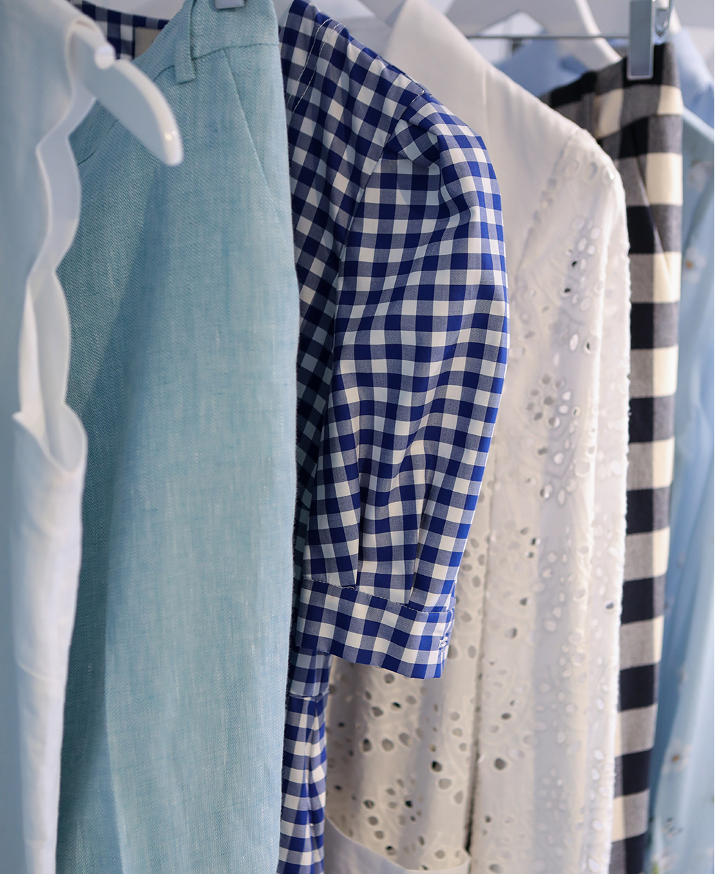A rail of summer appropriate clothes in on tren gincham check and pale blue linen