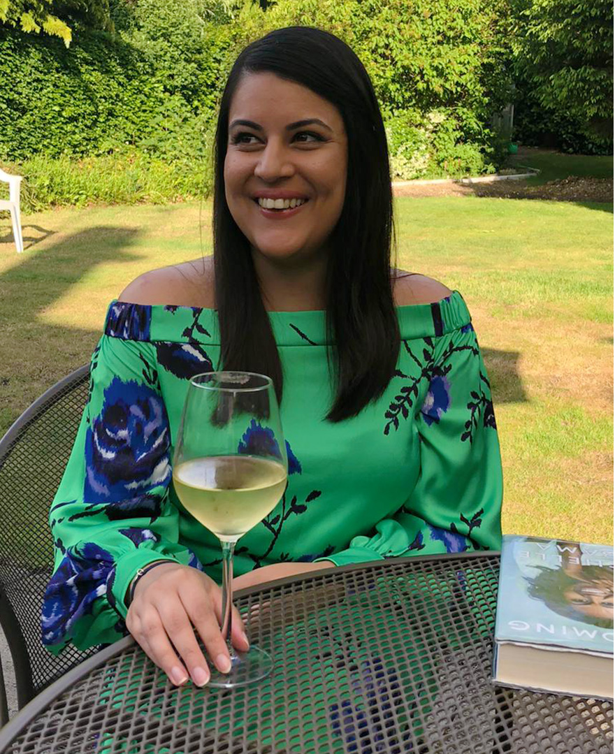 Hobbs junior womenswear buyer, Priya Banwait at home in the Hobbs green off shoulder Miriam dress
