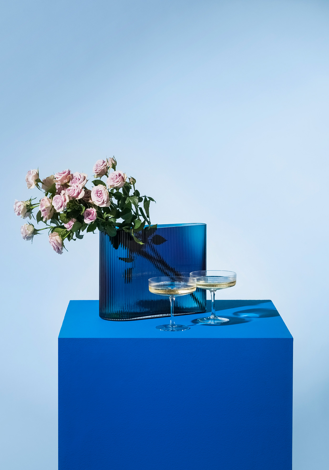 Spruce Up your fizz with two champagne coupes styles with a cobalt blye vase and dusky pale pink roses.