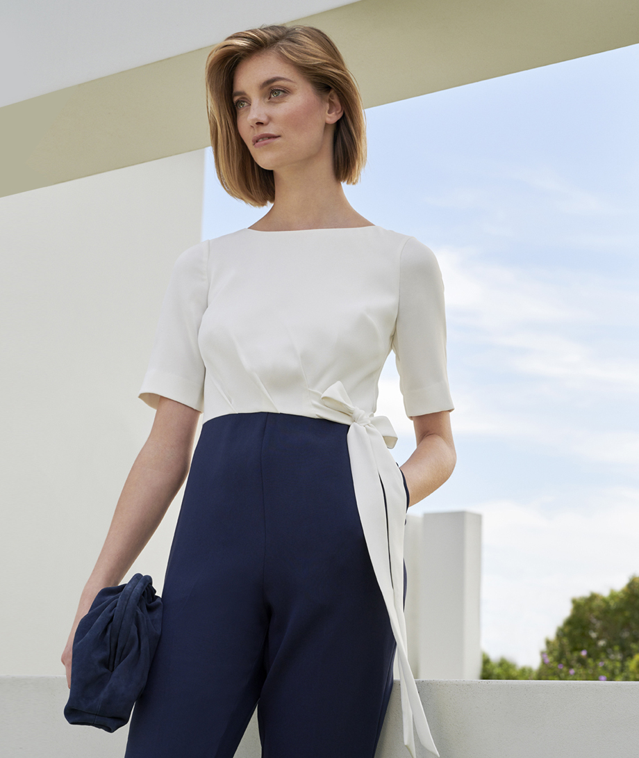 Colourblock jumpsuit in white and navy with waist tie detail, paired with a matching clutch in navy by Hobbs.