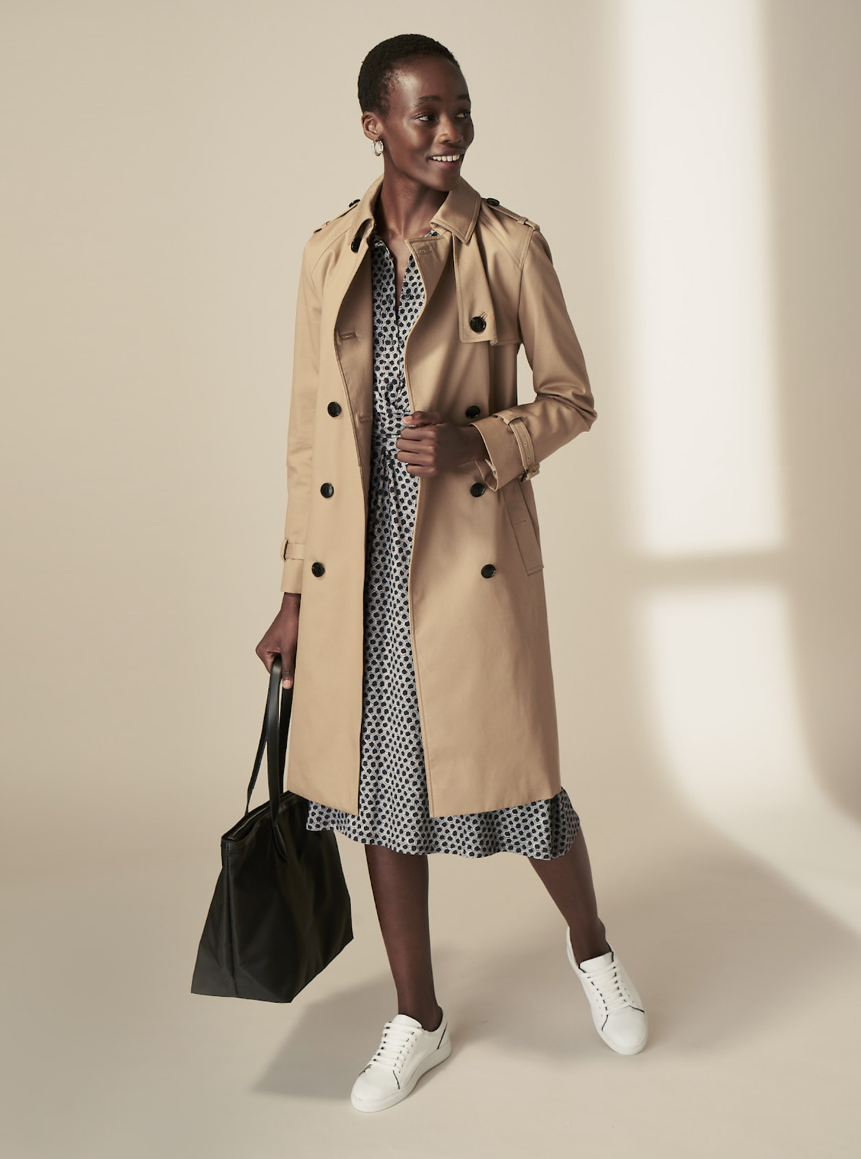Hobbs model wearing a beige trench coat over a midi dress, styled with white trainers and a black tote bag.