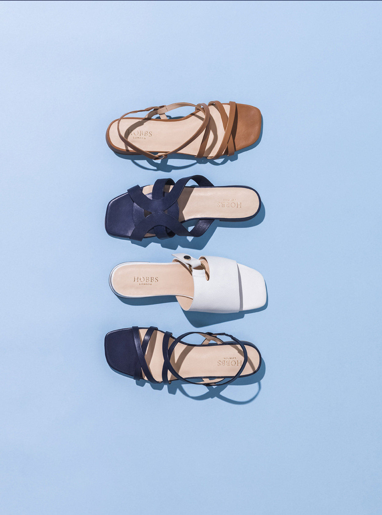 Four summer sandals from Hobbs against a blue background, from top to bottom: Brown sandal, dark blue sandal, white sandal, black sandal.