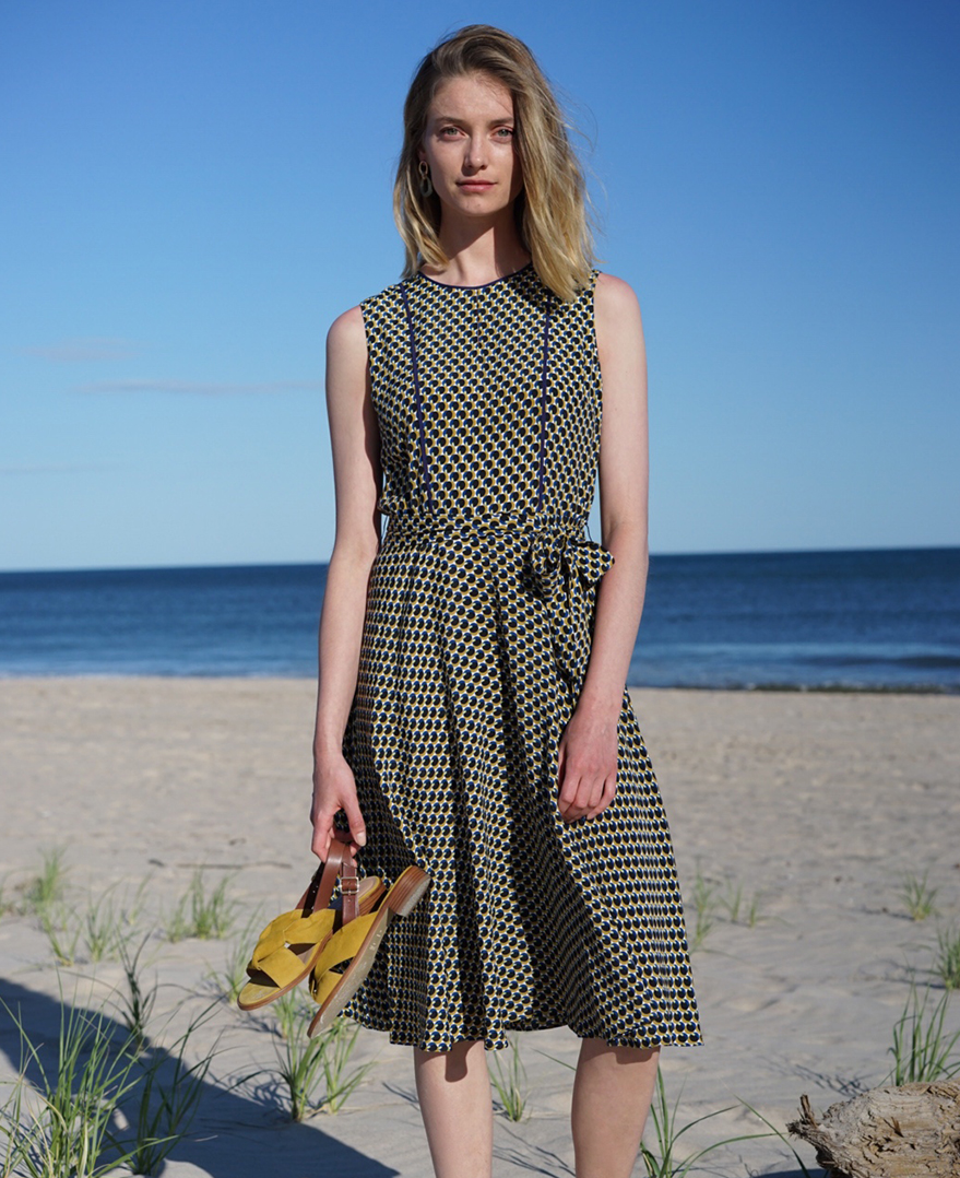Iris poses in a blue geometric sleeveless dress with yellow suede sandals in hand on the beach.
