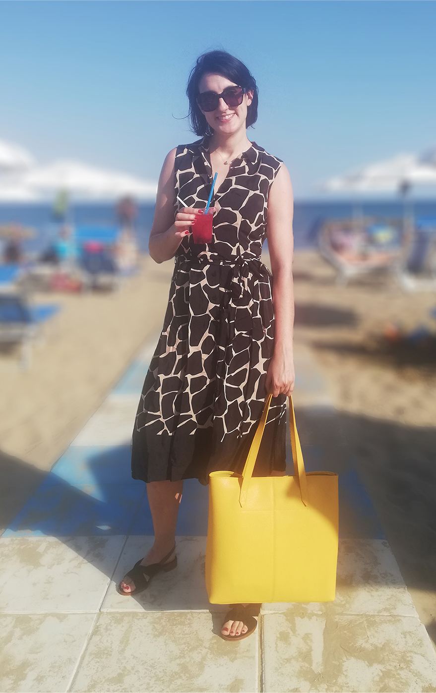 Marta Bonfaci, Senior Ecommerce Assistant, stands by the seaside holding a drink while wearing a sleeveless fit and flare shirt dress with an animal print, styled with a yellow tote bag and black slingback sandals.