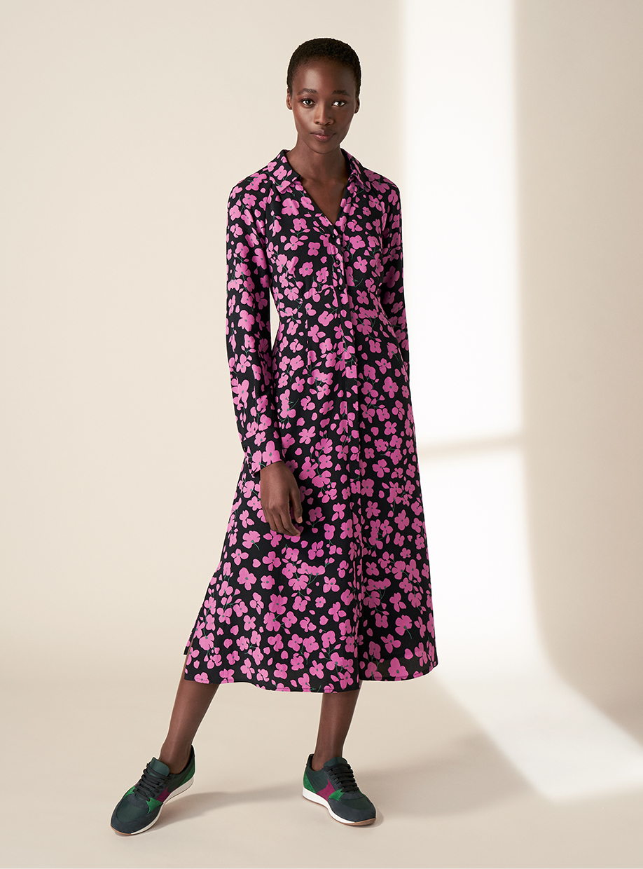 Model wearing the Hobbs Lulu navy and pink floral print shirt dress with trainers.