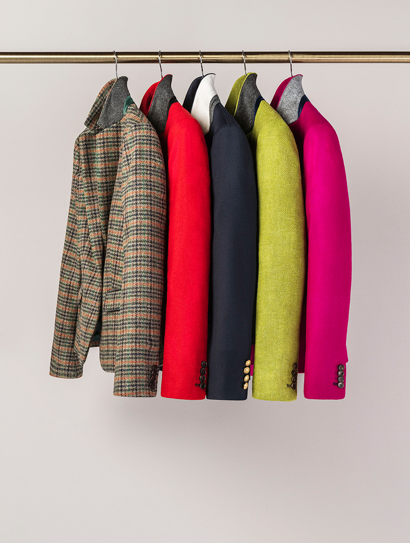 An image of a rail featuring Hobbs jackets made from Abraham Moon's British made sustainable fabrics. From left to right: Check, red, blue, green and pink.