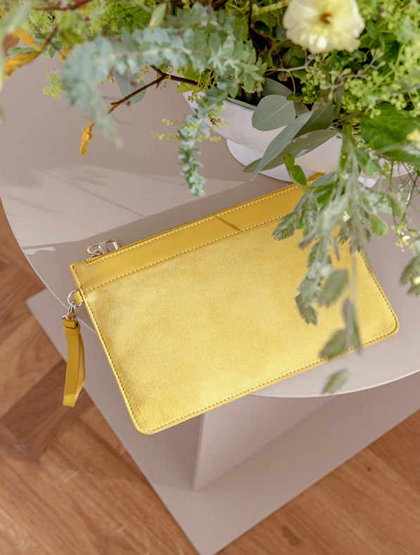 Yellow Wristlet Bag on Glass Table with Flowers