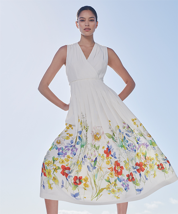 Woman poses in an elegant white midi dress with a floral motif along the bottom edge